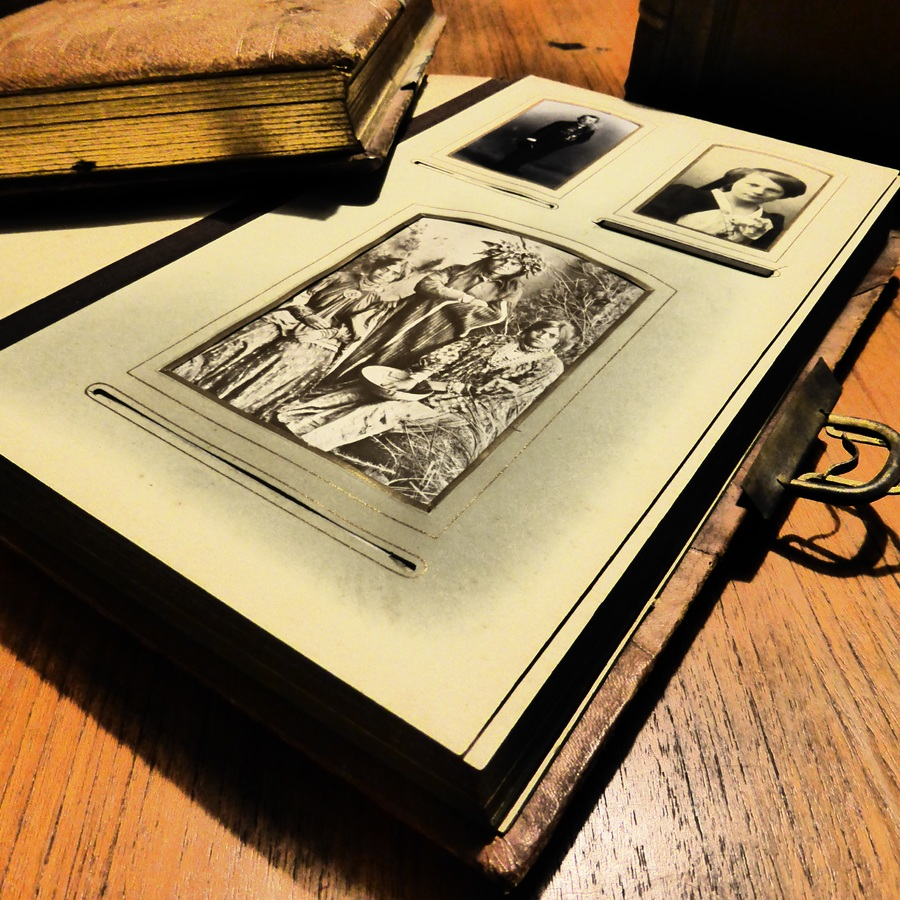 A open page of an old photo album laying flat with another book on an old wood desk with a bright light overhead