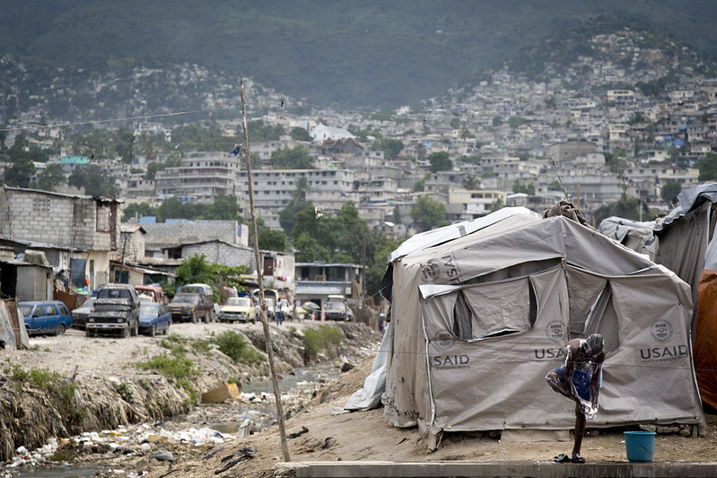 A series of USAID tents with a young man showering in front, several buildings and cars on the left side, and numerous white concrete buildings on a mountainside in the background