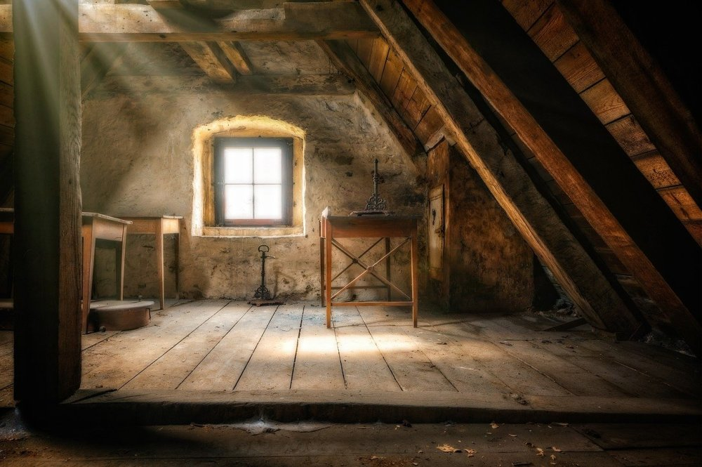 A photo of part of the inside of an old attic with an angled wall, three small tables, a small well-lit window, and sunbeams streaming down from a skylight in the roof