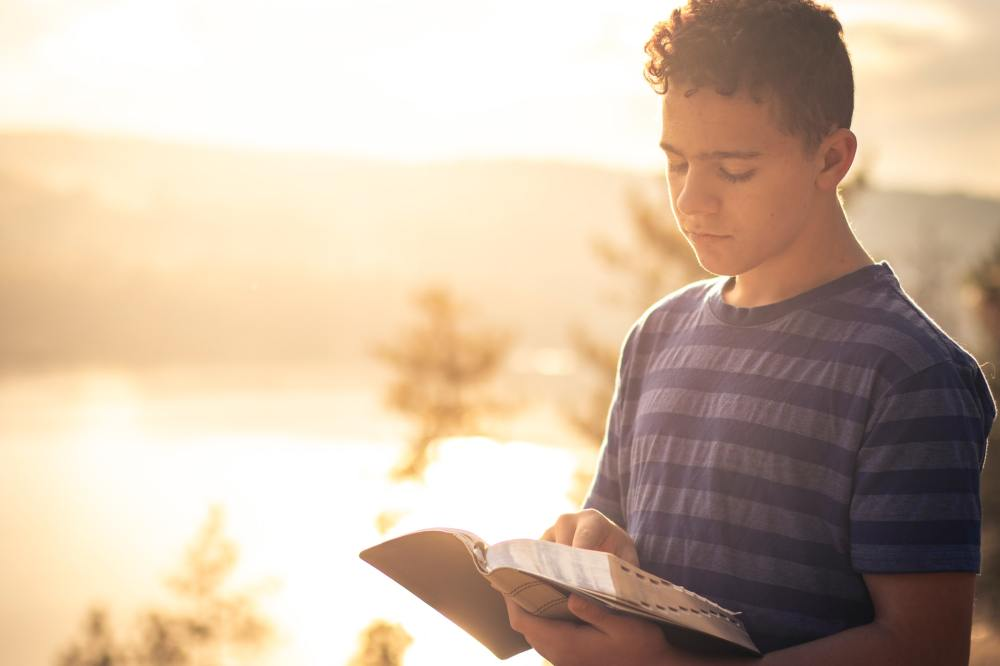 Young male teen wearing a grey and black striped shirt standing and looking down while reading a Bible in his left hand with bright sunlight and a distant mountain in the background