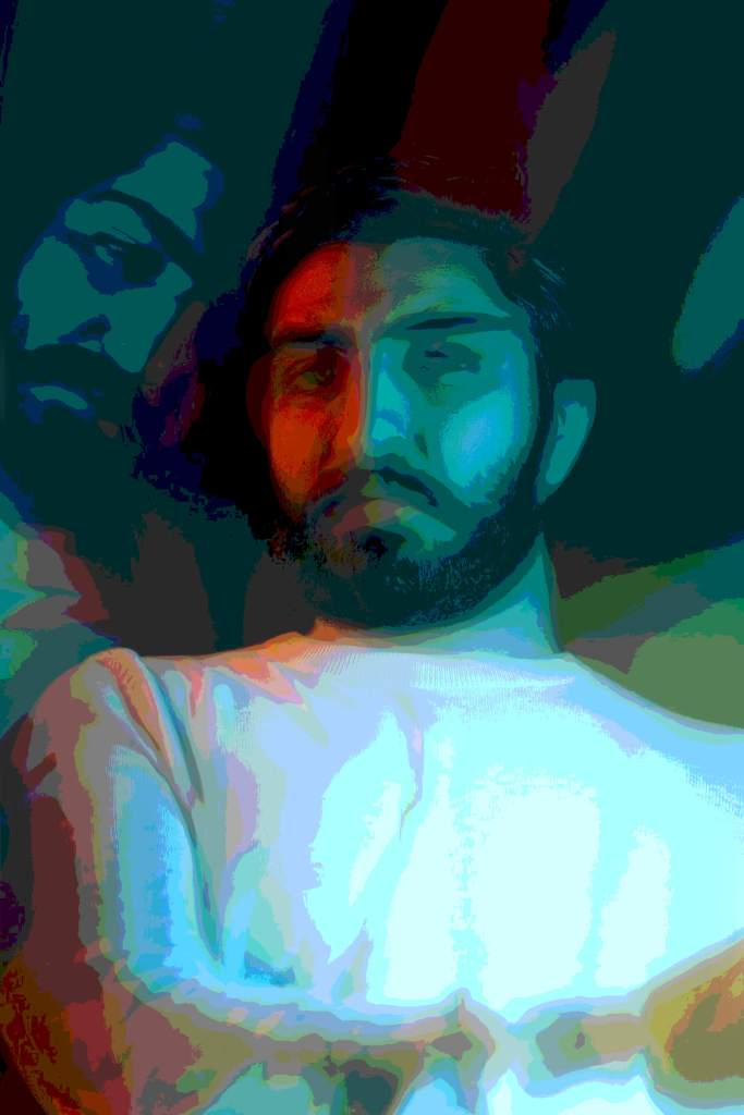 A posterized image of an Asian man with a straight face wearing a white mock turtleneck sweater with his arm fold across it and a partial side reflection of his face