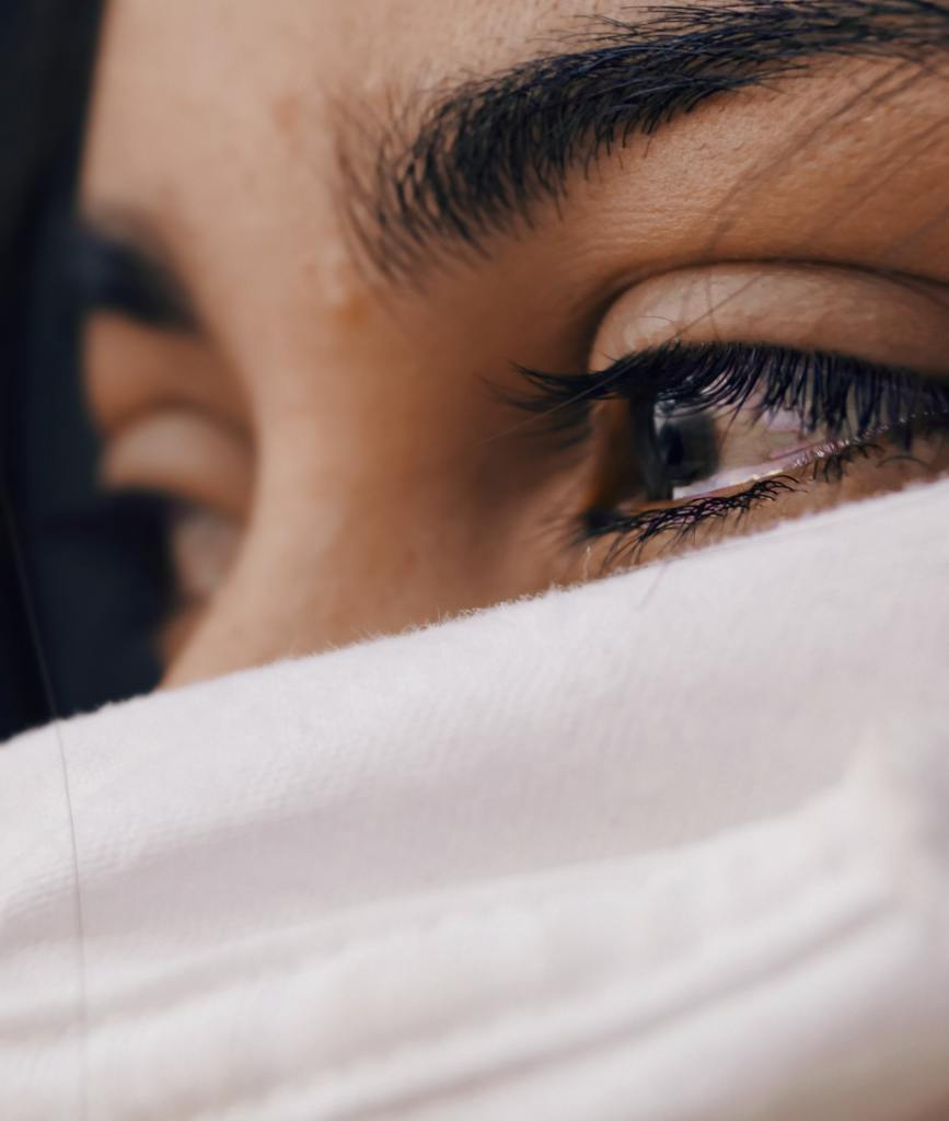 A close up photo of a woman's eyes and forehead with a white cloth veiling the rest of her face