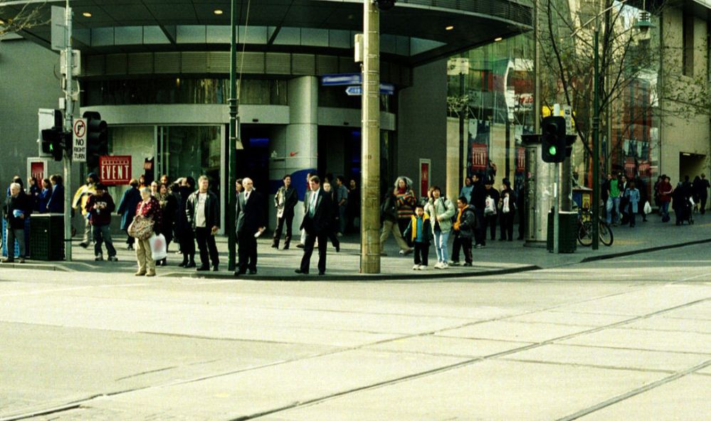 A large group of assorted people on a street corner in front of a department store in a city on a sunny fall day