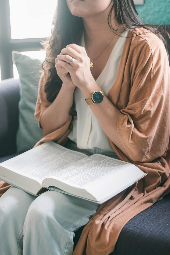 A photo cropped at the neck of a young woman wearing a white shirt, tan cardigan style outerwear, and pale blue jeans with her hands folded together and raised toward her chest while seated in a chair with a Bible on her lap