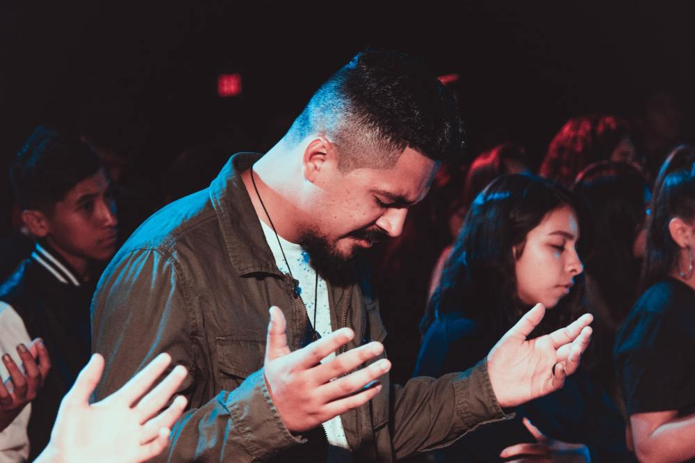 A Hispanic man with his bowed, eyes closed, and hands raised in worship along with others both male and female in the background of a partially darkened room