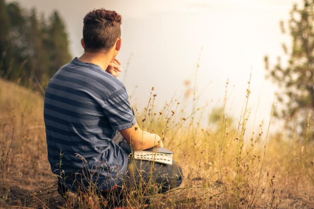 A young Caucasian man wearing a blue and grey striped short sleeved shirt holding a Bible while squatting down in a grassy sloped field with trees and a white sky in the background