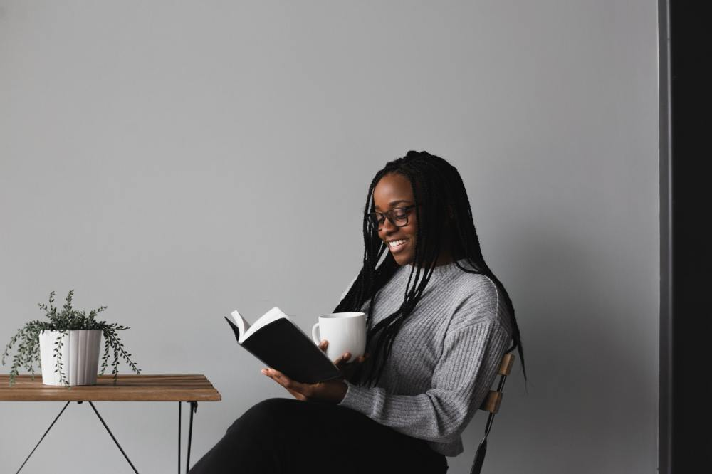 A photo of a young smiling African-American woman wearing a grey sweater and black pants sitting in a chair against a white wall in front of a small wire-framed, wood-topped table supporting a plant while reading a book and holding a white mug