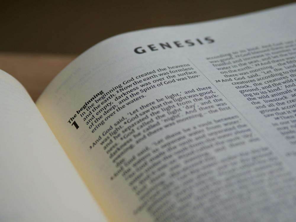 A Bible opened to the first chapter of the book of Genesis with lower portions of it out of focus