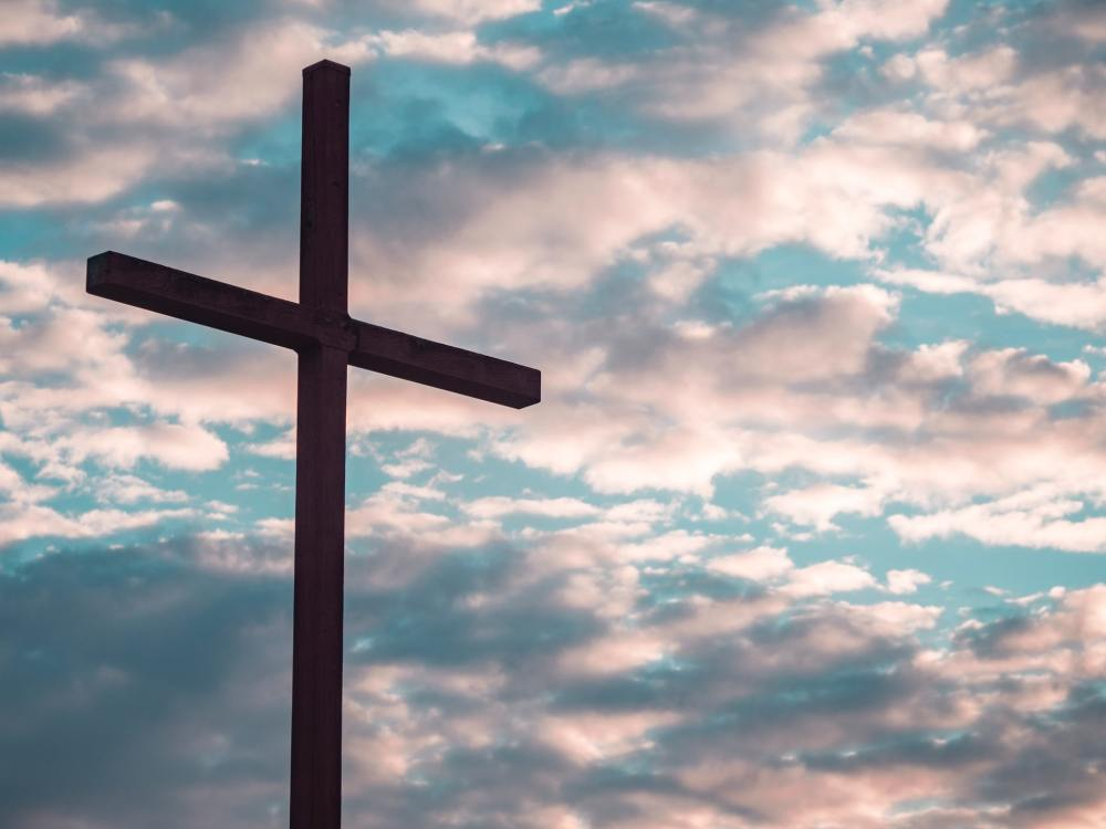 A photo of a silhouette of a cross against slightly pink tinted clouds and blue sky