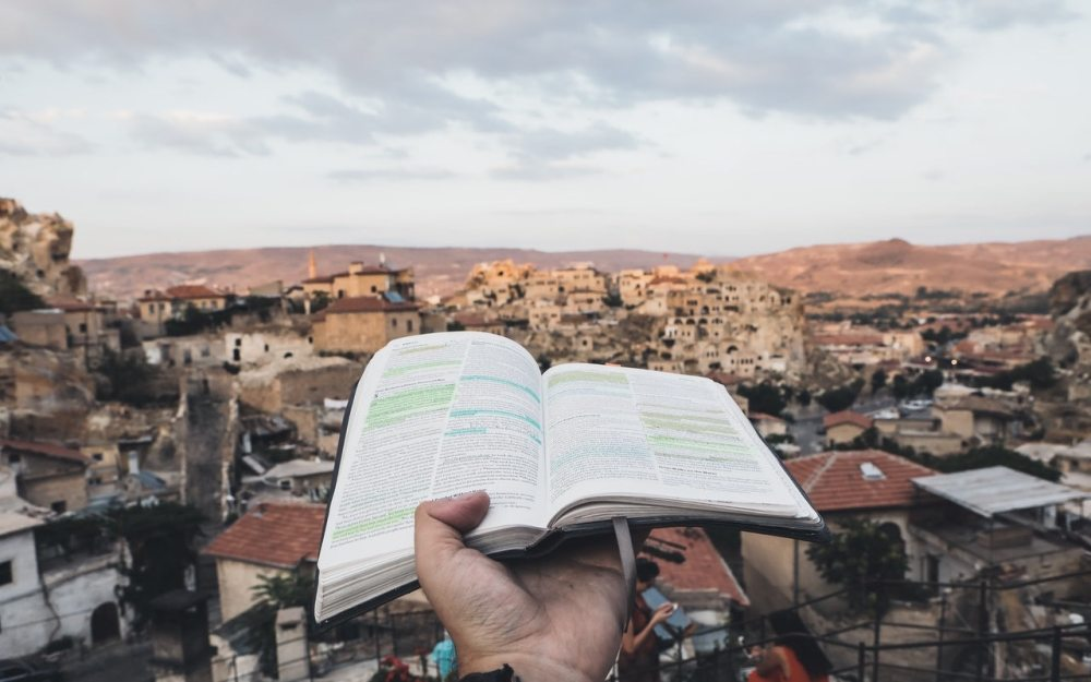 A single hand holding up a open book with underlining onto a Mediterranean type city and countryside