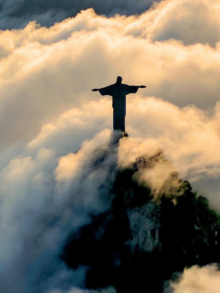 A photo of a statue of Jesus high on a mountain top surrounded in clouds and sunlight