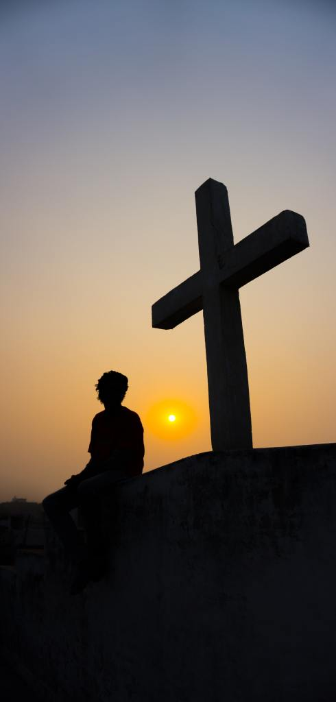 A silhouette of a man seated near a cross on a small hill with a setting sun in the background in a cloudless sky