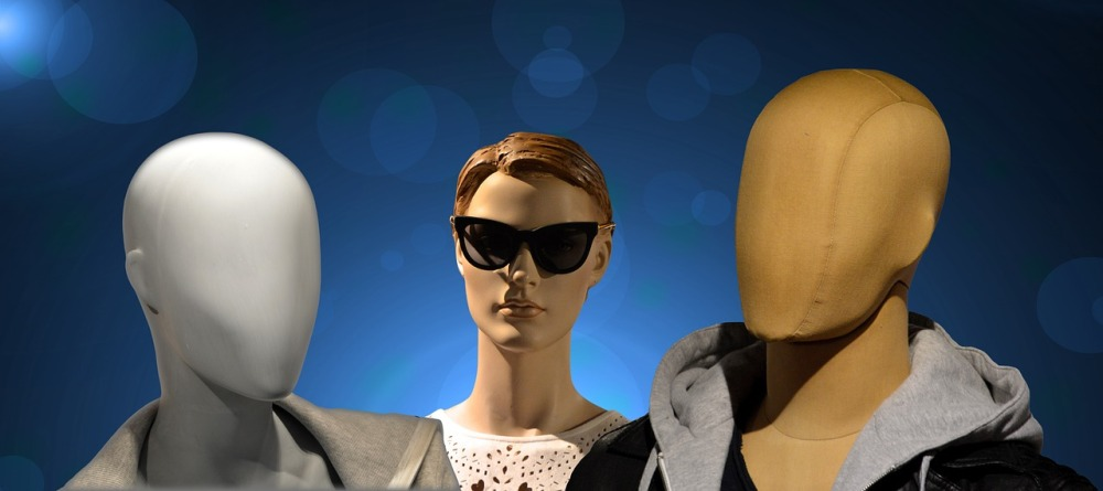 A graphical image of three mannequin headshots with one on the left having a blank grey face, the one in the center with parted brown hair and and facial features while wearing sunglasses, and the one on the right having a featureless tan face while wearing a hooded sweat jacket