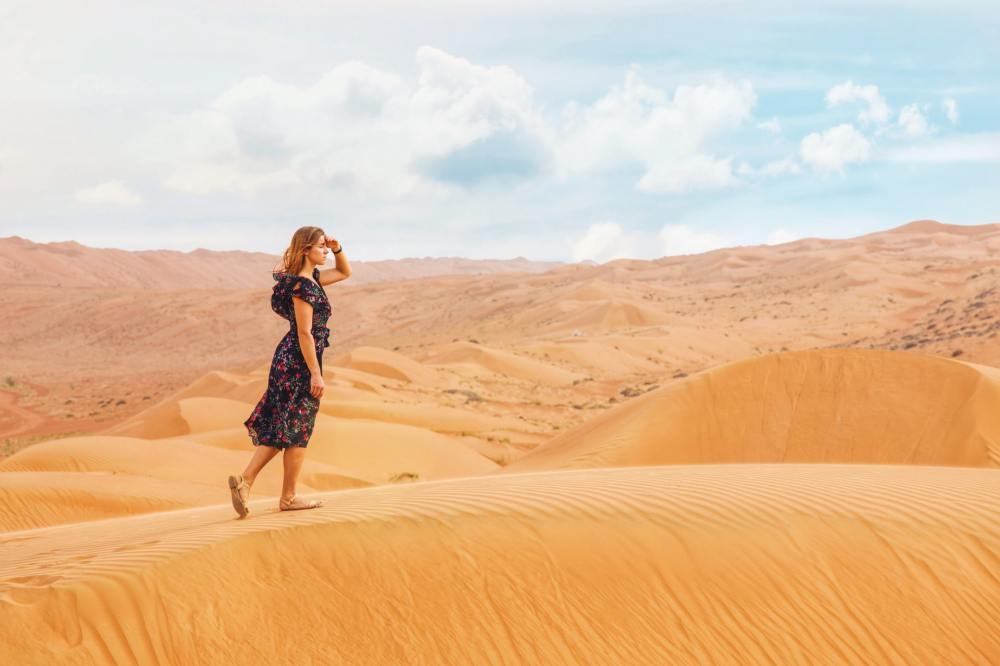 A young Caucasian woman wearing a dark flower print dress while walking on a dune in a desert with her left hand held up to her eyes as she looks forward and hazy clouds on a blue sky in the background