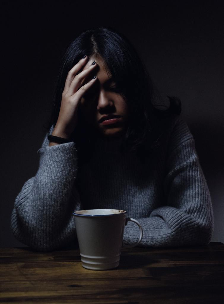A young African or Asian woman wearing a grey sweater seated at a table in a darkened room with a coffee cup in front and her right hand held up against her forehead and her eyes closed