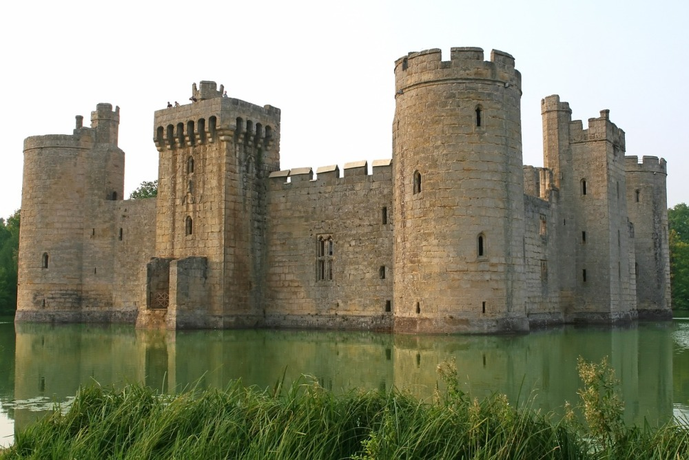 A large stone castle sitting in the middle of a green pond with grasses in the foreground and a pale sky overhead