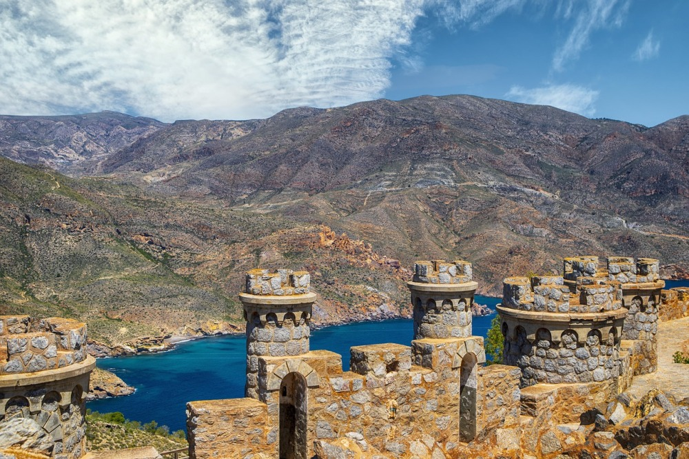 Looking out across the top of a stone castle surrounded by mountains, dark blue water, and a partially clouded blue sky