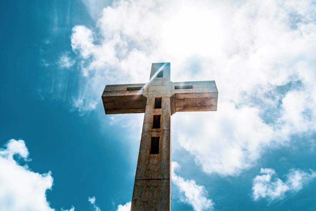 Looking up at a large cross against a blue sky with many white clouds and bright white sunlight