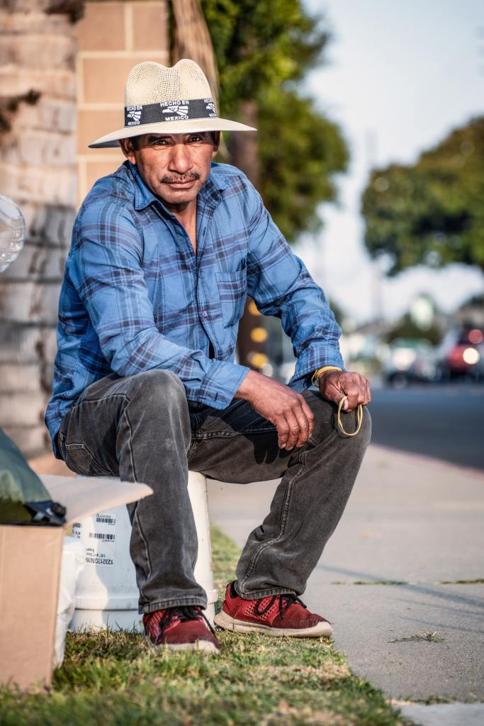 An older Hispanic man wearing a white hat, blue long sleeved shirt, black pants, and red shoes seated on an overturned white bucket alongside a street while facing the camera