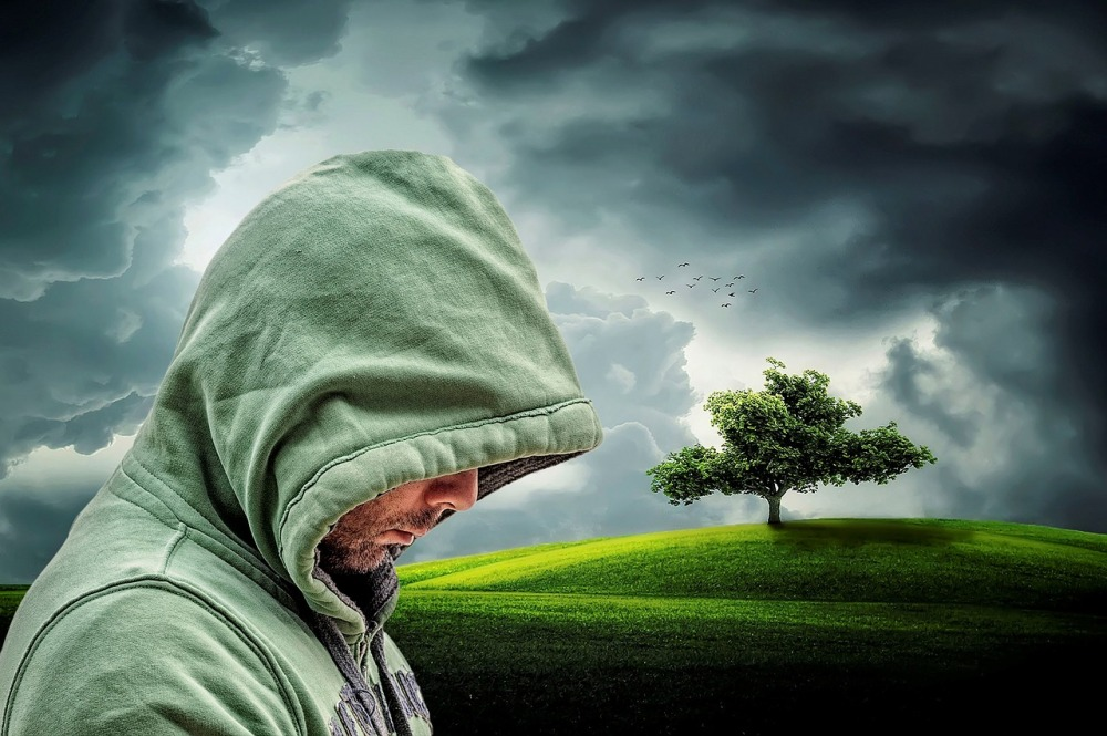 A graphical image of a man in a light emerald green hooded sweat shirt looking down while hidden in hood with a clouded sky, a partially lit hill, and tree in the background