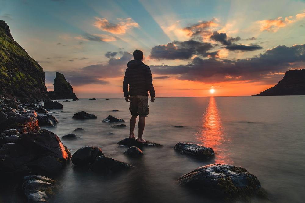 A partial silhouette of the backside of a man wearing a hooded jacket and shorts standing on one of a series of rocks near the rocky shore of a large body of water while looking at a sunset with a small mountain and clouds in the distance