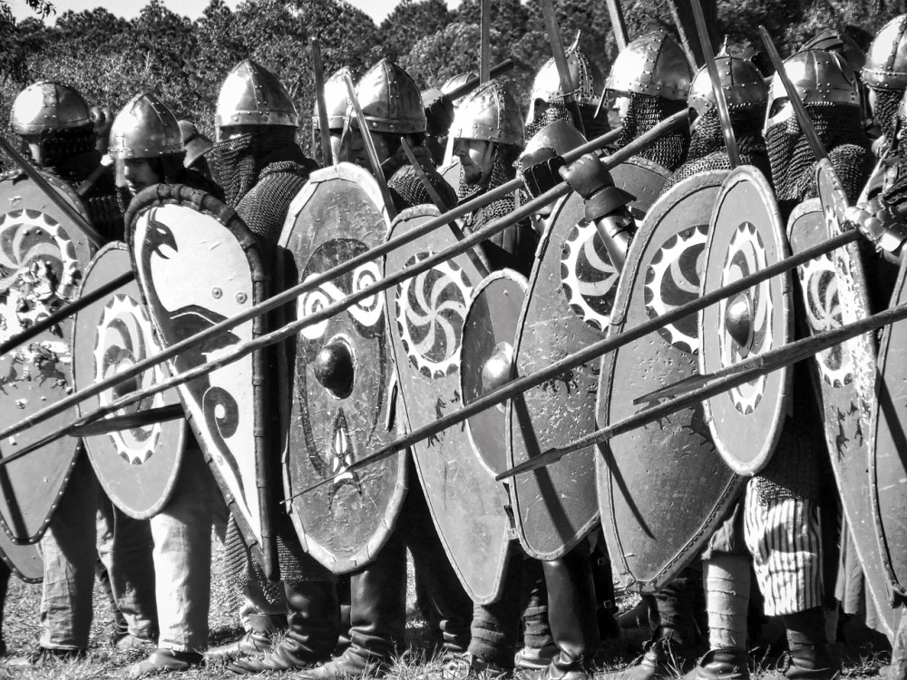 A black and white photo of a group of Medieval solders in full battle gear including swords, spears, and shields containing various crests