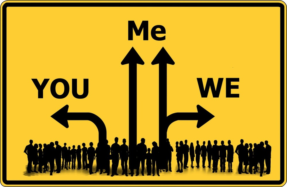 A graphical image of a road sign displaying single arrows pointing right and left with words 'you' and 'we' respectively and double arrows pointing upwards with the word 'me' above and a silhouette of a large group of people at the base of the arrows