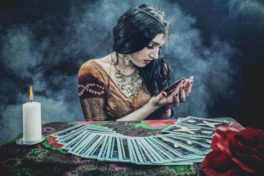 A Caucasian female fortune-teller with long black hair and a light brown dress seated in front of a table filled with an array of tarot cards, a candle, and a red rose while looking down at one of the cards held up in her hands