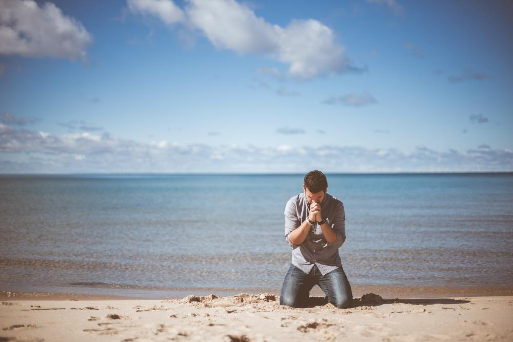 A man with black hair, light grey shirt, and blue jeans kneeling with his head bowed, hands raised and clasped together on a beach in front of a large calm body of water and a lightly clouded blue sky in the background