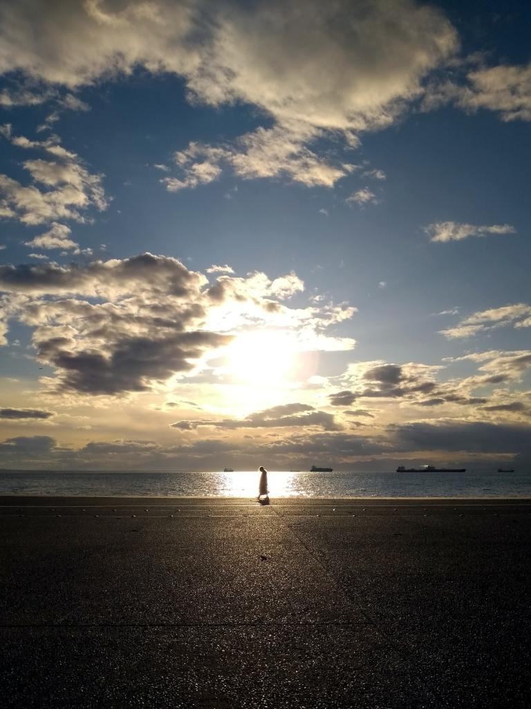 A setting sun, partially obscured behind clouds in a blue sky over a large body of water, highlighting a man walking on the sandy shoreline