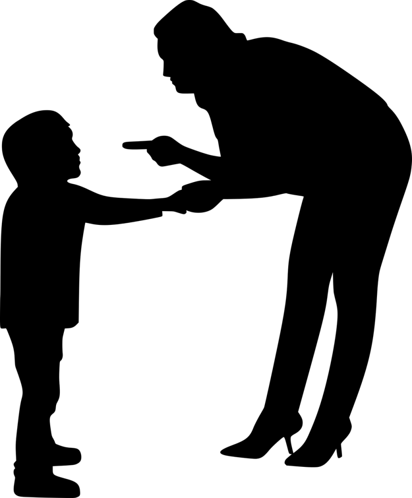 A silhouette of a woman bent over while pointing her left index finger at and holding the hand of a small boy standing in front of her