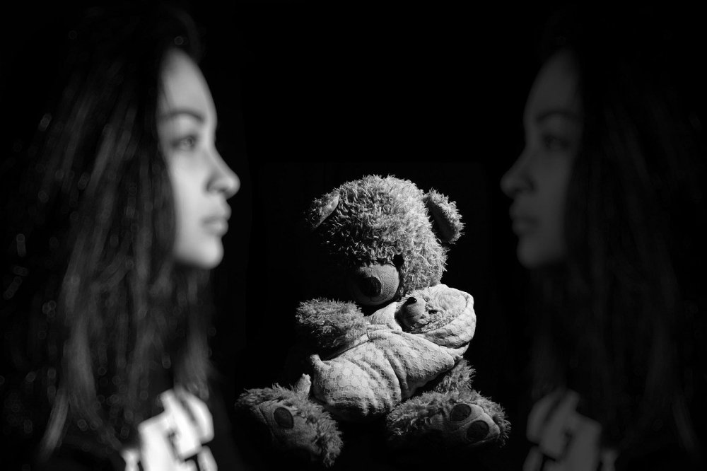 A black and white photo of a small stuffed bear located front and center between a young African-American woman looking to the right and a muted reflection of herself looking left